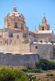 St. Paul`s Cathedral, Mdina, Malta. The view of the St. Paul`s Cathedral in the old capital Mdina surrounding by the fortress wall from the countryside below Stock Images