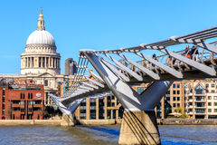 St Paul's Cathedral and the Millennium Bridge in London. London, England - April 20, 2016 - St Paul's Cathedral and the Millennium Bridge with tourists and local stock photo