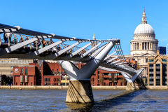 St Paul's Cathedral and the Millennium Bridge in London. London, England - April 20, 2016 - St Paul's Cathedral and the Millennium Bridge with tourists and local royalty free stock image