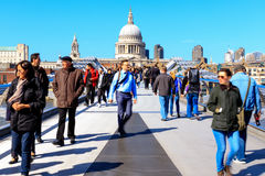 St Paul's Cathedral and the Millennium Bridge in London. London, England - April 20, 2016 - St Paul's Cathedral and Millennium Bridge with tourists and locals royalty free stock image