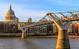 St Paul's Cathedral and the Millennium Bridge in London. Panoramic view of St Paul's Cathedral and the Millennium Bridge in London with warm light from sunset stock image