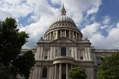 St. Paul`s Cathedral. London view looking up from the ground with a bright sky and lovely clouds and green trees Stock Photography