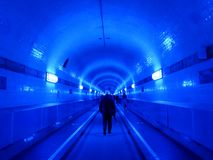 People in the blue illuminated Elbtunnel, in Hamburg, Germany Royalty Free Stock Image