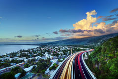St Pauls Bay on Reunion Island. Scenic view Bay of Saint Paul with colorful slow motion effect traffic lights on highway in foreground, Reunion Island stock photo