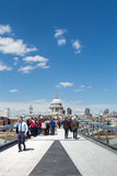 St Pauls Cathedral and bridge. LONDON, UK - MAY 13, 2015: Tourists and commuters walk on the Millennium bridge with St Pauls in the background on a sunny summer Stock Photos