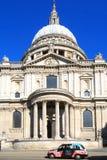 St. Pauls Cathedral an einem hellen Sommertag, mit einem ikonenhaften London-Taxi im Vordergrund Stockfoto