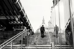 St Pauls Cathedral Man Walking Steps. Man in business suit walking up steps towards St Pauls Cathedral in London England in black and white Stock Images