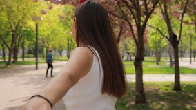 1st person view, woman follow me in a park holding my hand stock footage