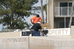 Workmen painting a keep off sign on a seawall. stock photography