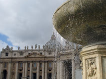 St. Peter's Basilica, Vatican, Rome. A view of St. Peter's Basilica in Rome through one of the fountains in the Vatican Square Royalty Free Stock Photos
