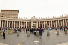 St. Peter`s, Bernini`s Colonade and the Maderno`s Fountain. Tourists around Bernini`s Colonade and the Maderno`s Fountain at St. Peter Basilica in Vatican City Royalty Free Stock Images