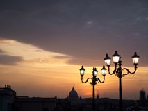 St peter's dome at sunset with street lamps. Beautiful view of St. Peter's Dome at sunset, colorful sky and lit up street lamps. Shot on Quirinale (Rome Royalty Free Stock Photography