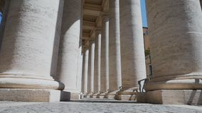 Best view through columns St. Peter`s Square, Rome,Vatican columns. St. Peter`s Square is a large plaza located directly in front of St. Peter`s Basilica in the stock video