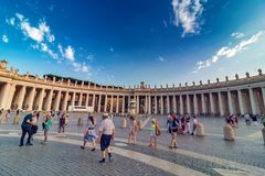 St Peter`s Square with tourists at sunset Stock Images