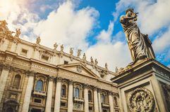St. Peter`s square, Vatican City, Roma. Low angle view of the statue of St. Peter with the front of the Basilica in the background royalty free stock photography