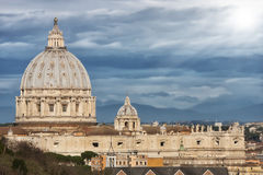 St. Peter (Vatican City, Rome - Italy). Clouds and sunlight. The dome of St. Peter view from the side. Lights and dramatic clouds with point of light and stock photography