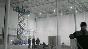 ST PETERBURG - 10 DECEMBER: mensen die in een groot modern pakhuis in aanbouw werken stock video