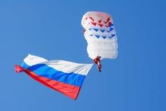 ST PETERBURG - Maj 9, 2015: Fallskärmshoppare i himlen med den ryska flaggan Royaltyfri Foto