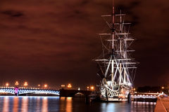 St.Peterburg. Russian ship. Russian ship in the night lights and bridge on background, St. Petersburg, Russia Stock Image