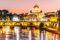 St Peters Basilica in Vatican and Ponte Sant`Angelo Bridge over Tiber River at dusk. Romantic evening cityscape of Rome stock photography