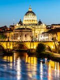 St Peters Basilica in Vatican and Ponte Sant`Angelo Bridge over Tiber River at dusk. Romantic evening cityscape of Rome royalty free stock photos