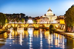 St Peters Basilica in Vatican and Ponte Sant`Angelo Bridge over Tiber River at dusk. Romantic evening cityscape of Rome royalty free stock image