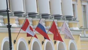 St Petersburg, Federación Rusa - 1 de julio de 2016: La bandera rusa y canadiense agita en el viento en un edificio, cierre almacen de metraje de vídeo