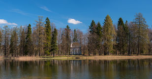 St. Petersburg, Gatchina Park, Pavilion of Eagle Island at White Lake. Trees and the pavilion reflected in the water Royalty Free Stock Images