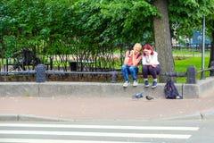 St Petersburg La Russia 07 10 2018 Giovani che alimentano i piccioni immagine stock
