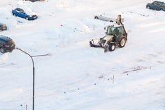 St Petersburg, Rússia - 31 de janeiro de 2019: O trator remove a neve no parque de estacionamento após uma queda de neve imagem de stock royalty free