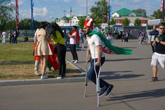 ST PETERSBURG, RÚSSIA - 15 DE JUNHO DE 2018: Fã iraniano nas muletas com pressa a obter ao fósforo no campeonato do mundo 2018 de Fotografia de Stock