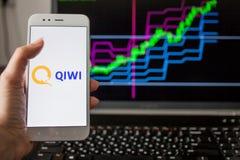 ST PETERSBURG, R?SSIA - 14 DE MAIO DE 2019: logotipo do qiwi da empresa do russo no fundo das cartas conservadas em estoque imagens de stock royalty free