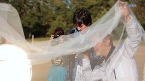 ST PETERSBURG, RÚSSIA - 19 DE SETEMBRO DE 2014: Fotógrafo que toma a foto de acenar o véu nupcial filme