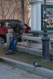St Petersburg, R?ssia, em abril de 2019 Pobre homem e pomba de sono do sono no ponto inicial de um restaurante chinês fotos de stock royalty free