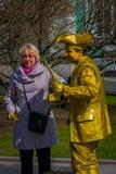 ST PETERSBURG, ROSJA, 01 2018 MAJ: Niezidentyfikowana para blisko do złotego farba mima artysty lub utrzymanie złotej statuy Zdjęcie Stock