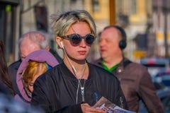 ST PETERSBURG, ROSJA, 02 2018 MAJ: Zamyka up blondynki kobieta jest ubranym czarną okulary przeciwsłoneczni ans czerni kurtkę, ch Fotografia Stock