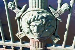 St Petersburg, Rusia, abril de 2019 La decoración de la cerca vieja del hierro bajo la forma de cabeza de un guerrero en el escu fotografía de archivo