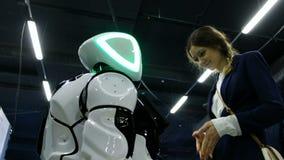 St Petersburg, Rusia - 12 de noviembre de 2018: La muchacha lee una pantalla del promo-robot almacen de metraje de vídeo