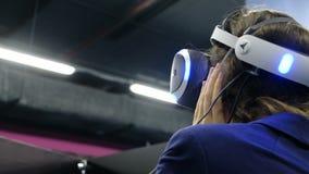 St Petersburg, Rusia - 12 de noviembre de 2018: La mujer de negocios con los vidrios de la realidad virtual juega a un juego metrajes