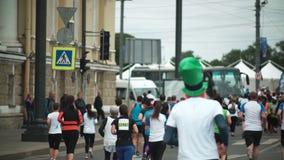 ST PETERSBURG, RUSLAND - 09 07 2017 Achtermening van mensen die marathon in de stad in werking stellen De mannen en de vrouwen ne stock footage