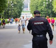 St. Petersburg, Rusland - Augustus 4, 2018: Een politieagentpatrouilles het park dichtbij het voetbalstadion stock afbeeldingen