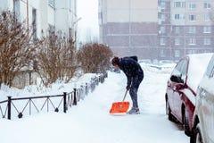 St. Petersburg, Rusland - Januari 17, 2019: Een mens maakt sneeuw in de yard met een schop na een zware sneeuwval schoon royalty-vrije stock foto