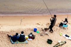 St. Petersburg, Rusland - Juli 10, 2018: De groep vissers vist op de zandige kusten van de Golf van Finland onder de brug royalty-vrije stock fotografie