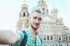 ST PETERSBURG, RUSSIA - agosto 2016: Uomo turistico felice davanti sulla chiesa russa storica del monumento Fotografie Stock