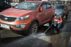 A worker washes the street in places where cars are parked. St. Petersburg, Russia - April 8, 2017: A male utility employee washes the roadside where cars are Royalty Free Stock Image