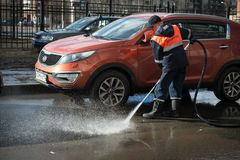 A worker washes the street in places where cars are parked. St. Petersburg, Russia - April 8, 2017: A male utility employee washes the roadside where cars are Stock Images