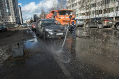 A worker washes the street in places where cars are parked. St. Petersburg, Russia - April 8, 2017: A male utility employee washes the roadside where cars are Royalty Free Stock Photo
