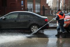 A worker washes the street in places where cars are parked. St. Petersburg, Russia - April 8, 2017: A male utility employee washes the roadside where cars are Stock Image