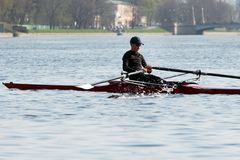 Rowing training - rower on the boat. St. Petersburg, Russia - April 26, 2019: young man rowing a single scull. rowing training on the Malaya Nevka river royalty free stock photo