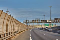 Cars on ring road with noise barrier fence royalty free stock photography
